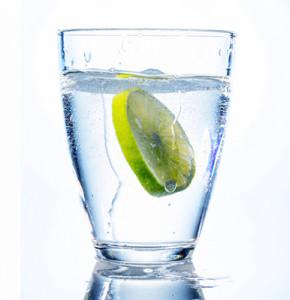 Ein Glas mit frischem Trinkwasser und einer Limette. Mineralwasser als Durstlöscher.